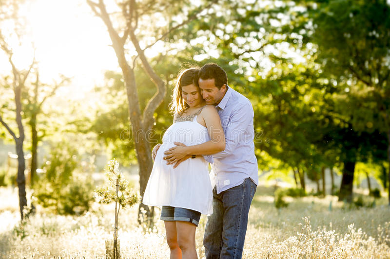 Young happy couple in love together on park landscape sunset with woman pregnant belly royalty free stock photos