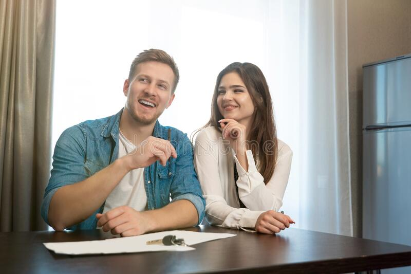 Young happy couple man and woman sitting in their new cosy apartment after successful lease sign both smiling royalty free stock photo