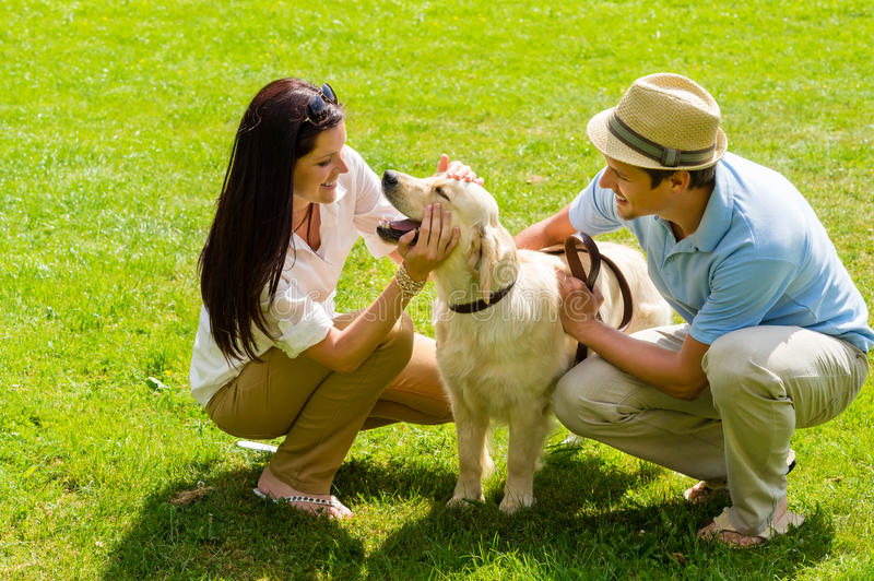 Young happy couple playing with Labrador dog stock images