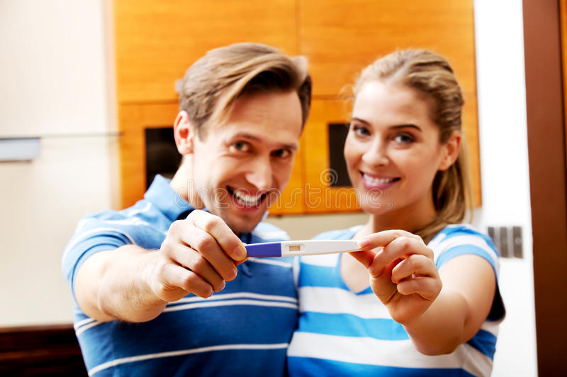 Young happy couple with pregnancy test standing in kitchen stock images