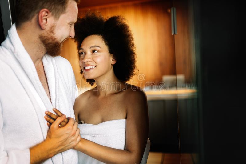 Young happy couple relaxing inside a sauna at spa resort hotel luxury stock photo