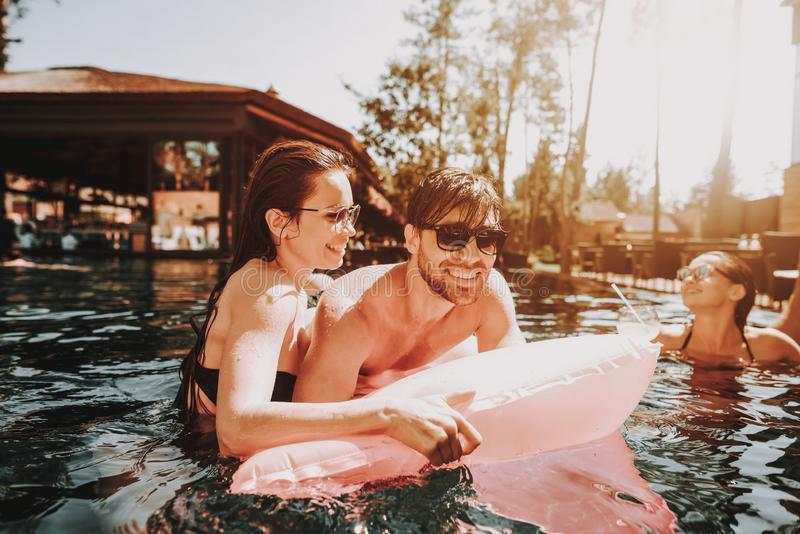 Young Happy Couple Resting on Air mattress in Pool royalty free stock photos