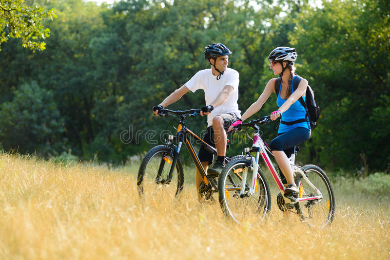 Young Happy Couple Riding Mountain Bikes Outdoor Royalty Free Stock Image