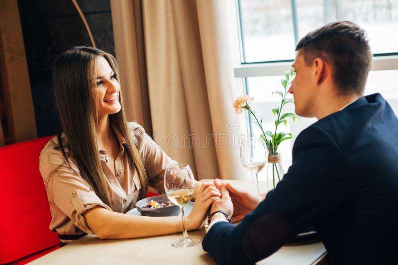 Young happy couple romantic date drink glass of white wine at restaurant, celebrating valentine day. Romantic couple dating in restaurant royalty free stock photos