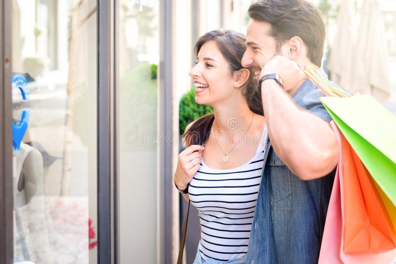 Cheerful young couple shopping together and looking shop windows royalty free stock photo