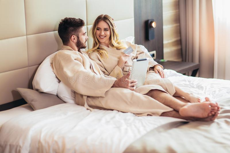 Happy couple shopping online in luxury hotel room stock images