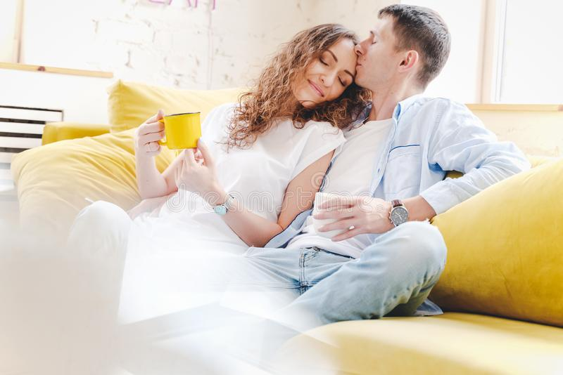 Young happy couple sit and cuddle on a yellow sofa in the apartment, love and tenderness, drink morning coffee and tea stock photo