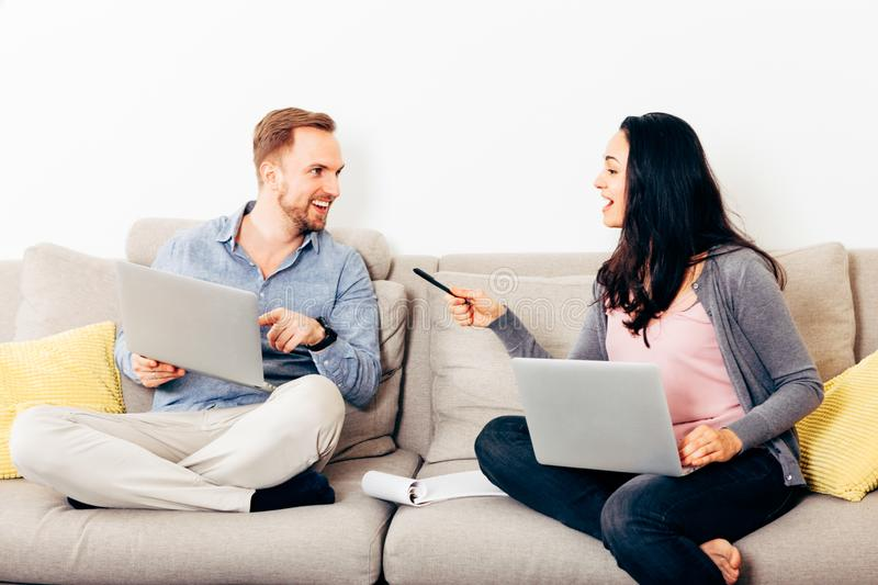 Young happy couple sitting on a couch with laptop. Male and female couple indoors sitting on a couch are happily discussing about something using laptops stock images
