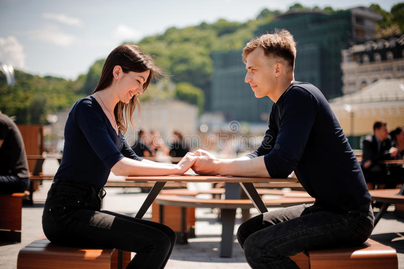 Young, happy couple smiling and holding hands across the table at a restaurant. royalty free stock photos