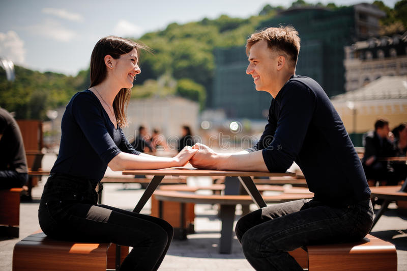 Young, happy couple smiling and holding hands across the table at a restaurant. royalty free stock image