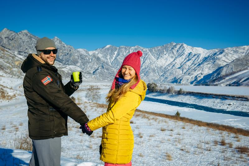 Young happy couple in snowy mountains with copy space. Guy and girl in bright clothes holding hands looking at camera and smiling stock image