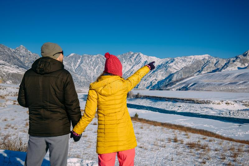 Young happy couple in snowy mountains with copy space. Guy and girl in bright winter clothes look at the snowy peaks. Christmas. Holidays stock image