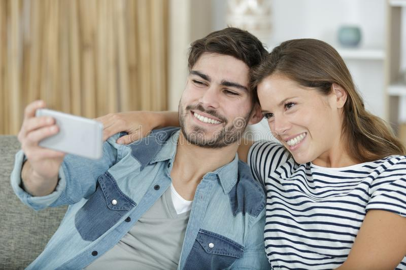 Young happy couple taking selfie on sofa stock image