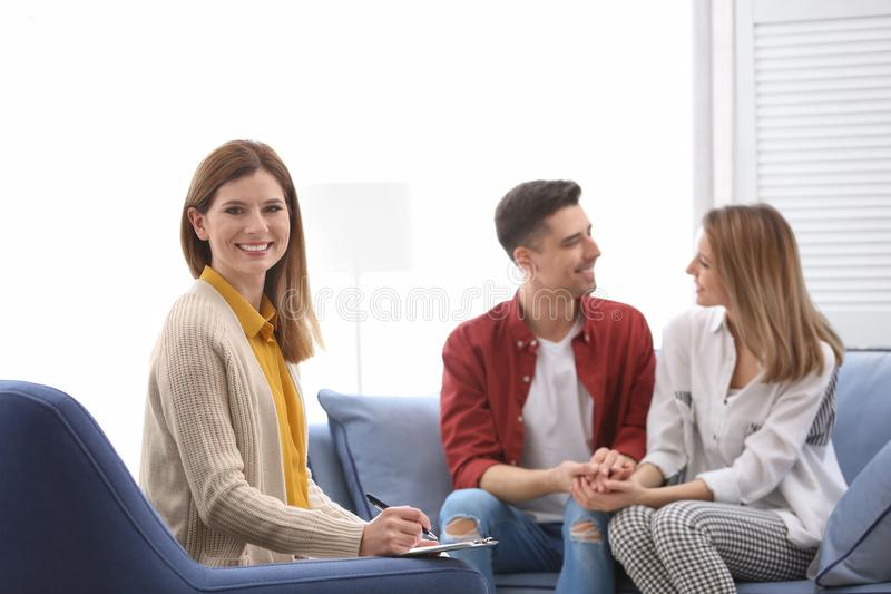 Young happy couple after therapy session. With family psychologist indoors stock photo