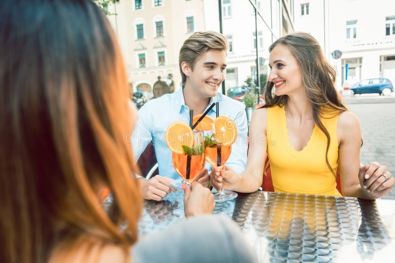 Happy couple toasting with their mutual female friend at a trendy restaurant. Young happy couple toasting with fresh orange cocktails with their mutual female royalty free stock photography