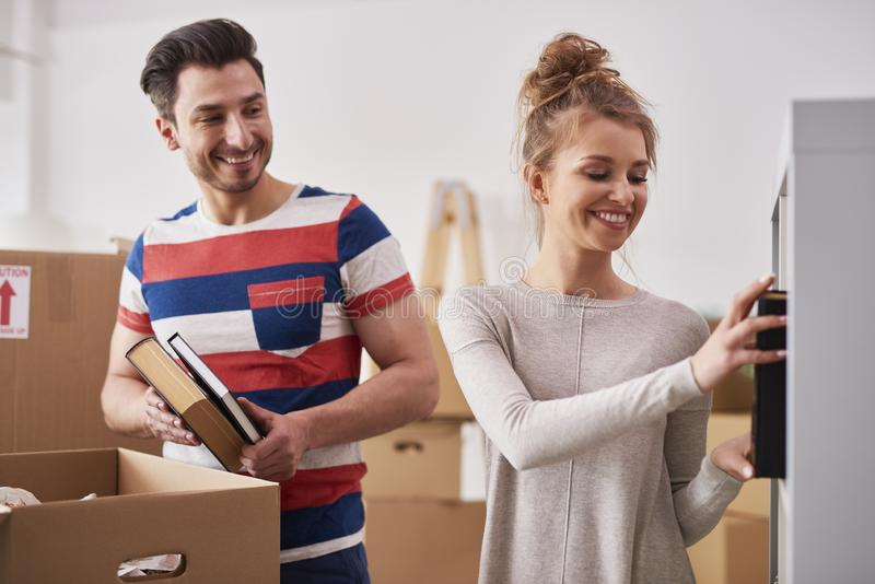 Young couple unpacking moving boxes in new flat stock photo