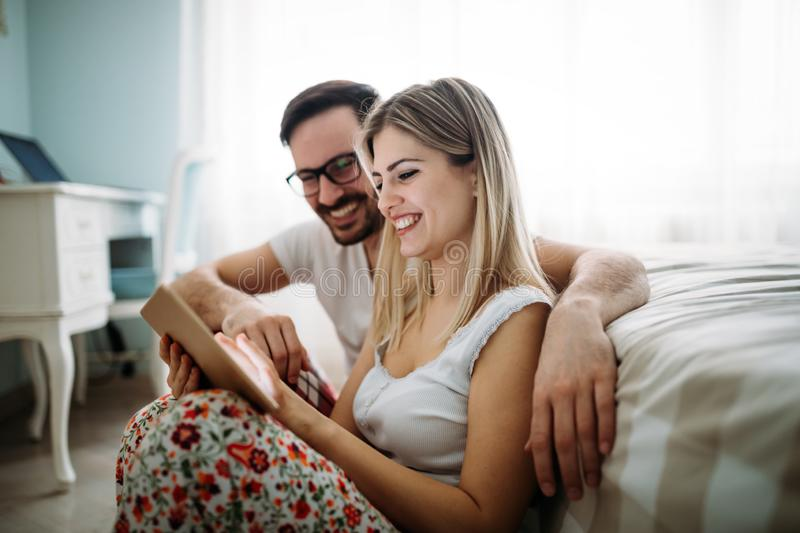 Young happy couple using tablet in bedroom royalty free stock photos