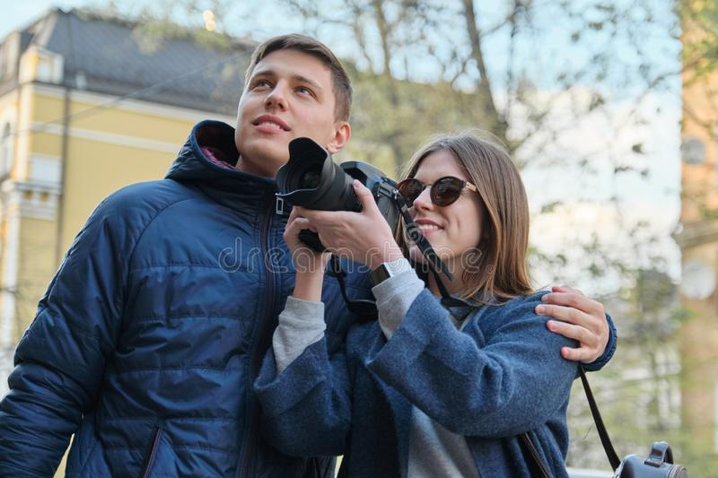Young happy couple walking through the streets spring city, attractive male and female tourists taking pictures with photo camera royalty free stock photography