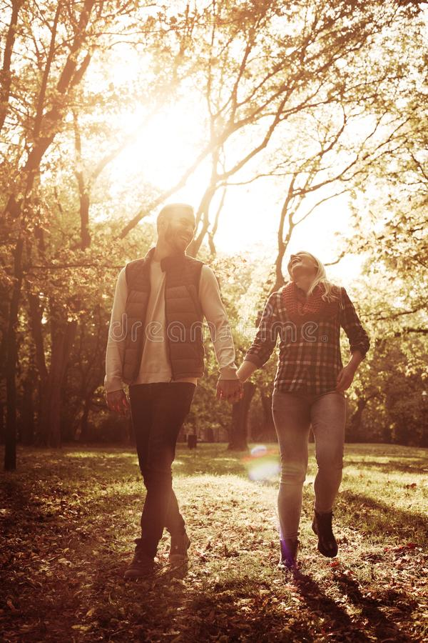 Young couple walking trough park and holding hands. stock photos