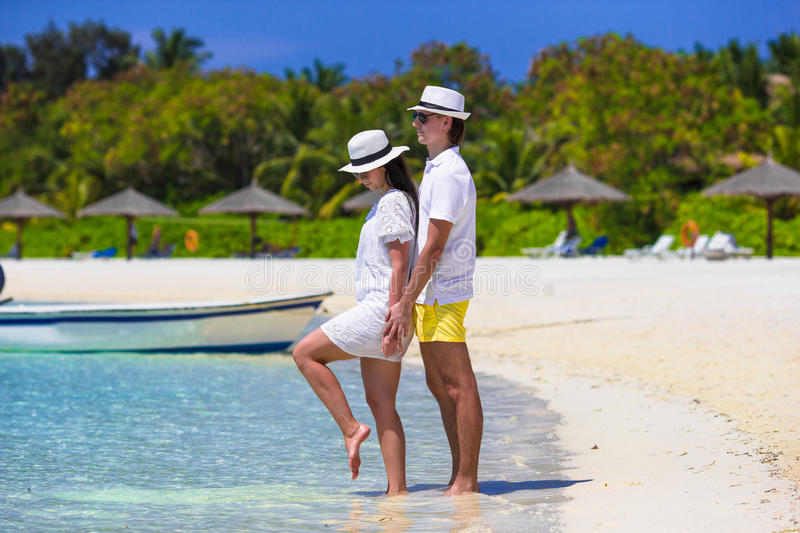 Young happy couple on white beach at summer. Young happy couple have fun on summer tropical vacation royalty free stock photo