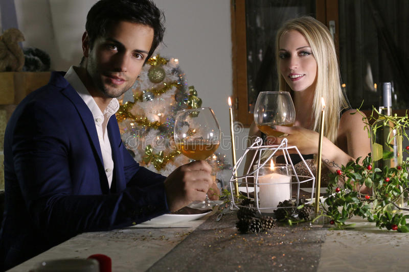 Young happy couple with a wine glasses at celebration. Attractive couple with a wine glasses at celebration at home stock image