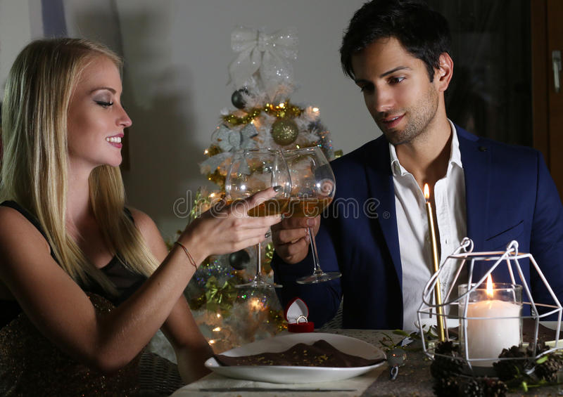 Young happy couple with a wine glasses at celebration. At home stock photography