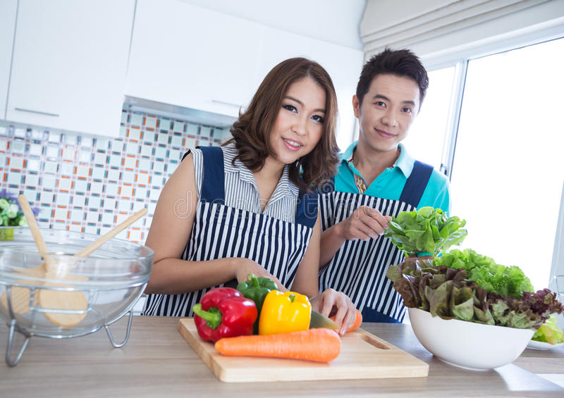 Couples in kitchen. Young happy couples in domestic kitchen royalty free stock photography