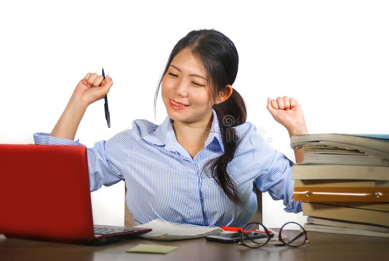 Young happy and cute Asian Chinese teenager student smiling happy working and studying with texbooks and laptop computer sitting stock photography