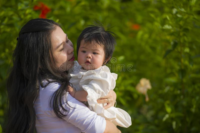 Young happy and cute Asian Chinese woman enjoying and playing with her baby girl daughter holding and kissing her smiling cheerful stock photo