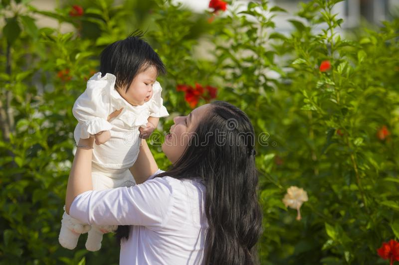 Young happy and cute Asian Chinese woman enjoying and playing with her baby girl daughter holding her raising up in her arms royalty free stock images