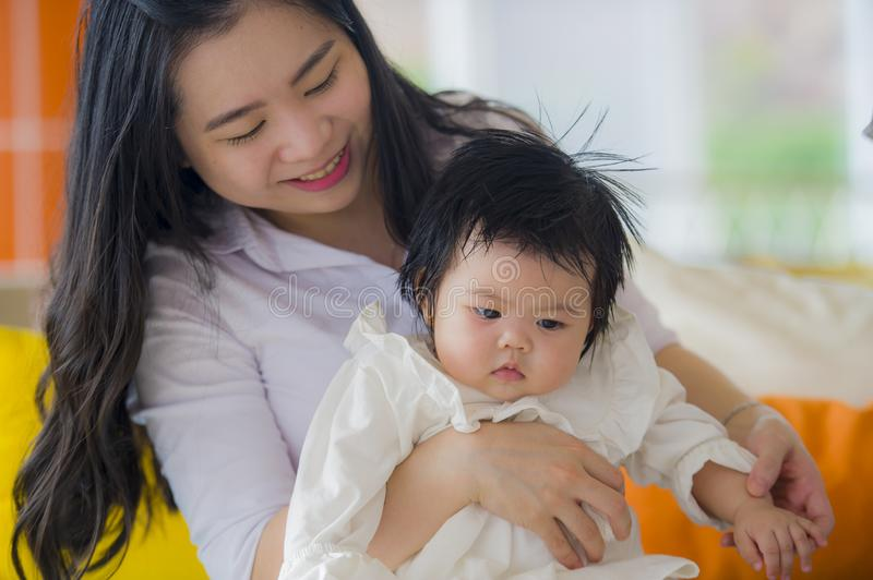 Young happy cute Asian Chinese woman holding baby girl sitting at holidays resort enjoying vacation trip in mother and little royalty free stock photo