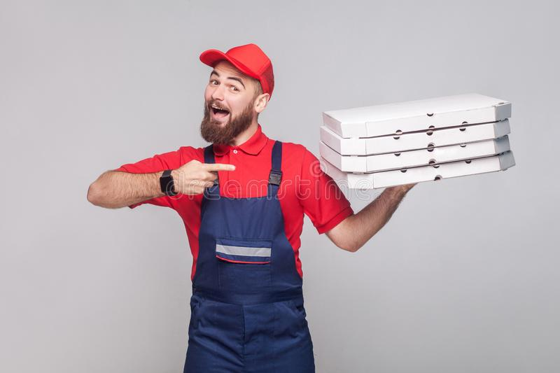 Young happy delivery man with beard in blue uniform and red t-shirt standing, holding and pointing finger to stack of cardboard p stock image