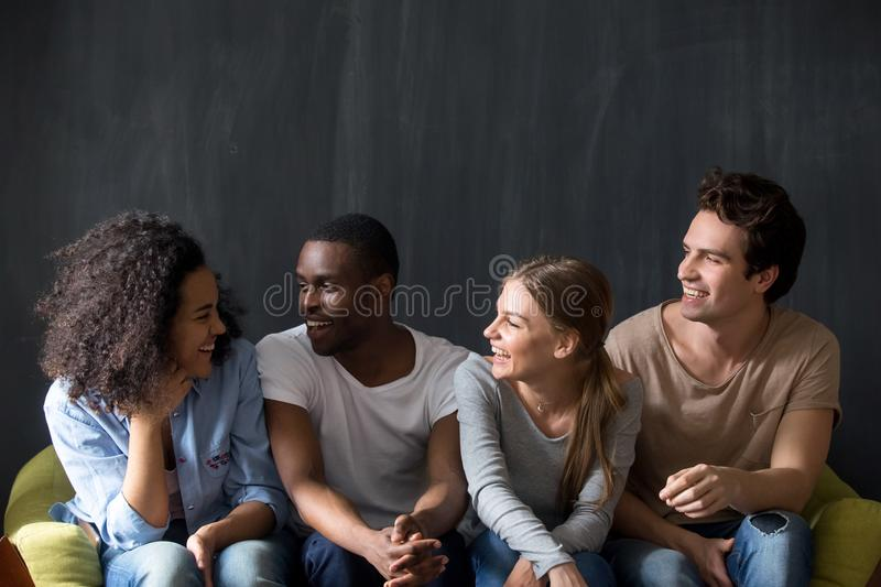 Young happy diverse friends listening to biracial smiling girls joke. royalty free stock photography
