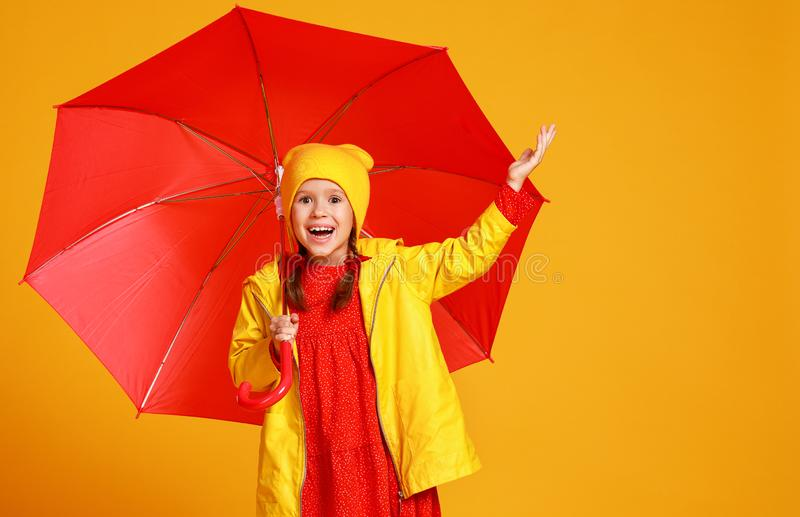 Happy emotional cheerful child girl laughing  with red umbrella   on colored yellow background royalty free stock images