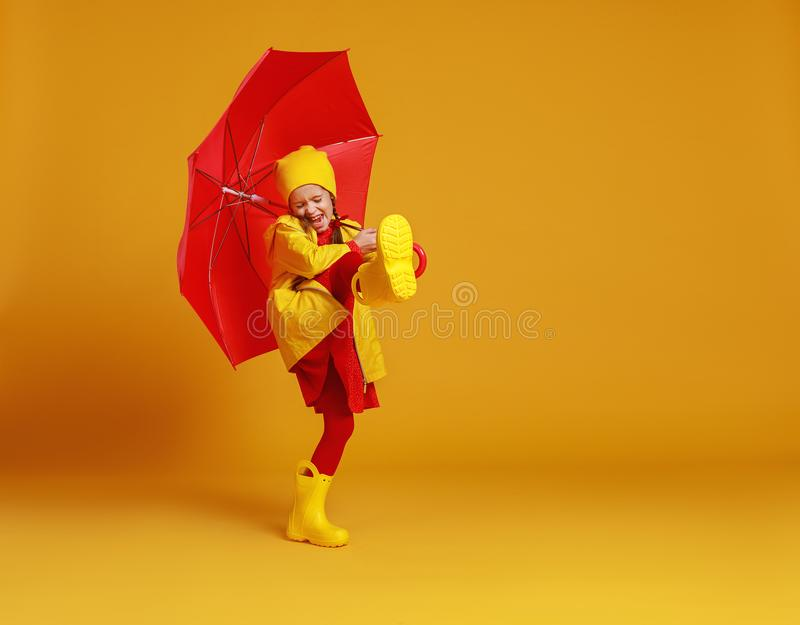 Happy emotional cheerful child girl laughing  with red umbrella   on colored yellow background royalty free stock photos