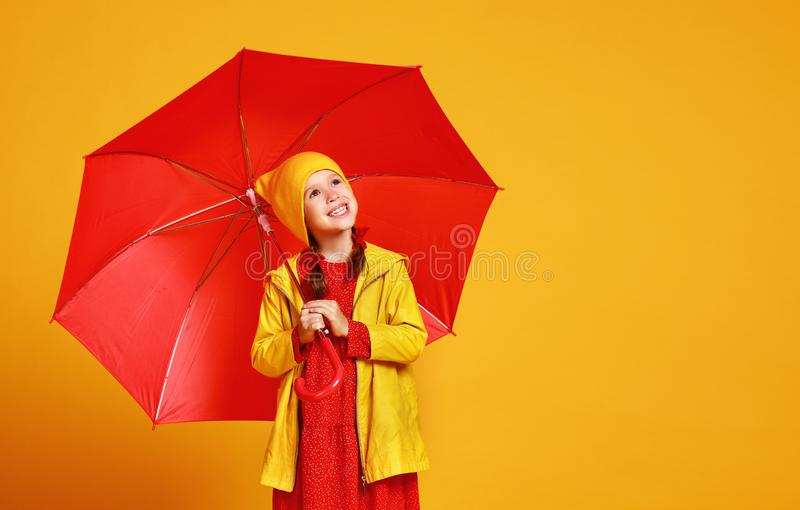 Happy emotional cheerful child girl laughing with red umbrella on colored yellow background stock photography