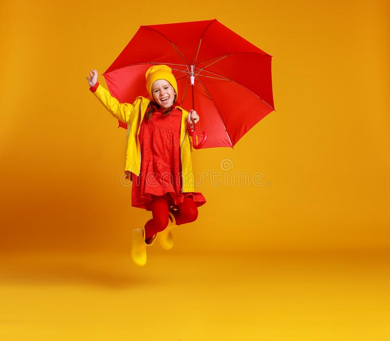 Happy emotional cheerful child girl jumping and laughing  with red umbrella   on colored yellow background. Young happy emotional cheerful child jumping and girl stock image