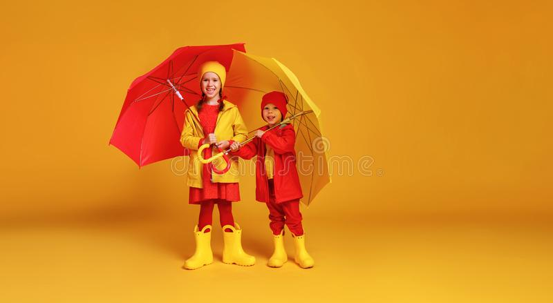 happy emotional cheerful children friends laughing  with red umbrella   on colored yellow background royalty free stock images