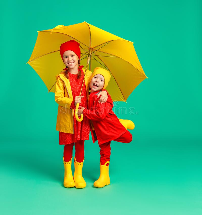 happy emotional cheerful children friends laughing  with yellow umbrella   on colored green background stock photography