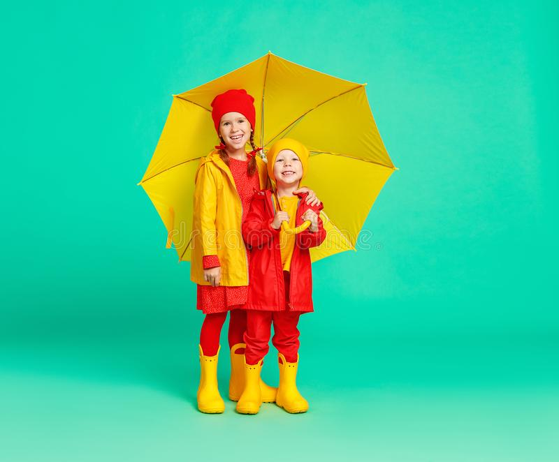 happy emotional cheerful children friends laughing  with yellow umbrella   on colored green background stock photos