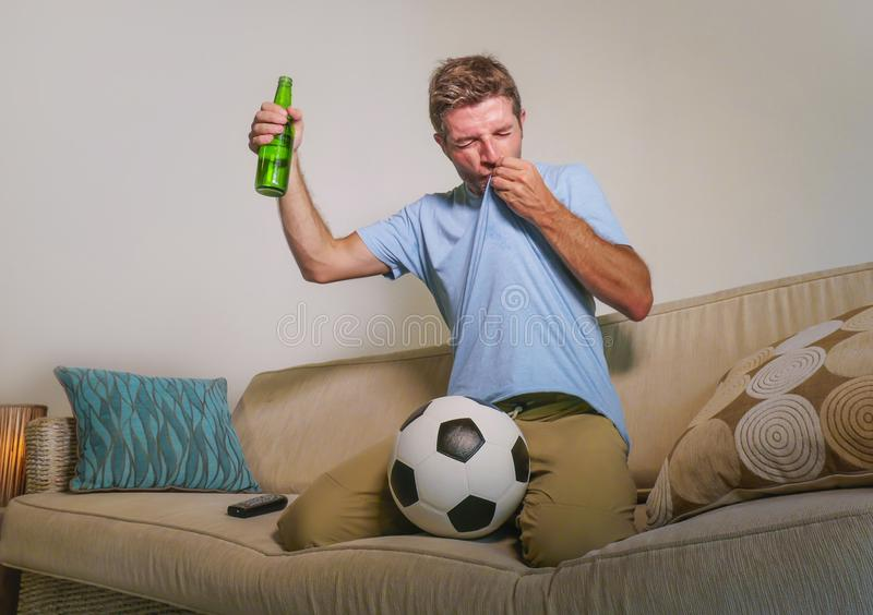 Young happy excited and crazy football fan man celebrating team scoring goal and victory watching game on television kissing socce royalty free stock photo