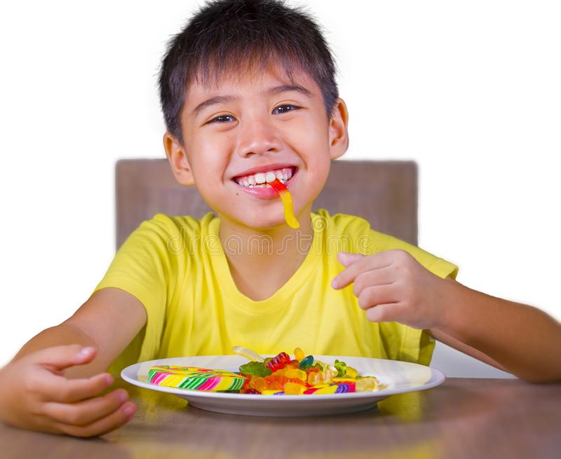 Young happy and excited male kid smiling cheerful eating dish full of candy and lollipop sitting at table isolated on white royalty free stock images