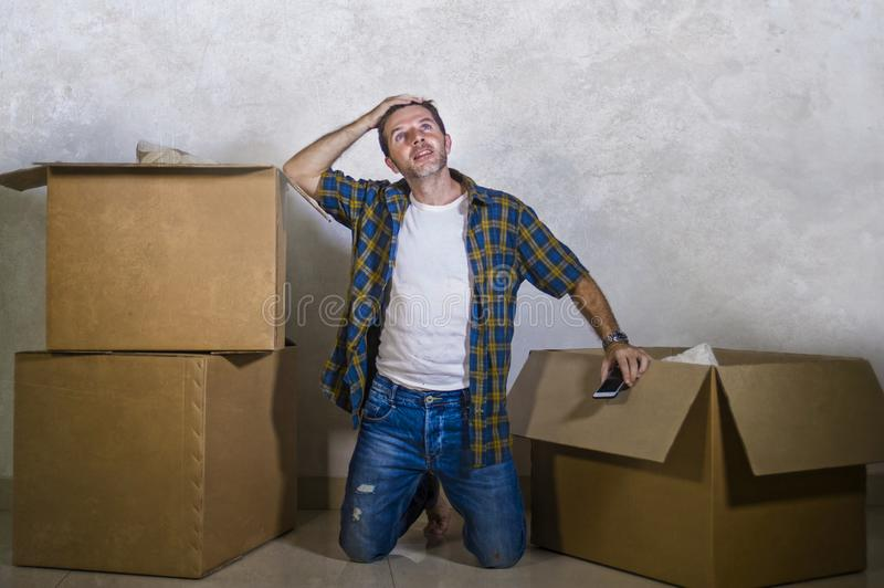 Young happy and excited man at home floor enjoying unpacking cardboard boxes moving alone to new apartment or house smiling stock images