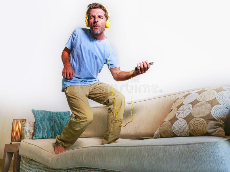 Young happy and excited man jumping on sofa couch listening to m stock photo