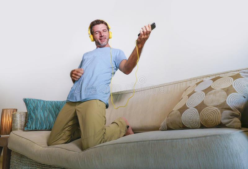 Young happy and excited man jumping on sofa couch listening to m. Usic with mobile phone and headphones playing air guitar crazy having fun at home living room stock image