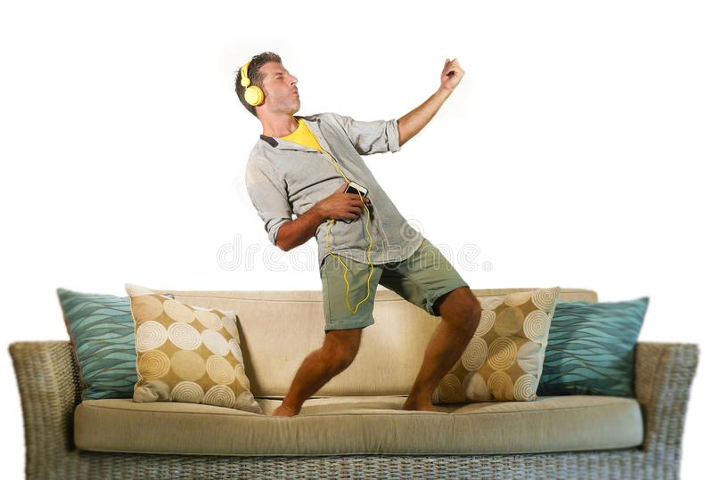 Young happy and excited man jumping on sofa couch listening to music with mobile phone and headphones playing air guitar crazy hav. Ing fun at home living room royalty free stock photo