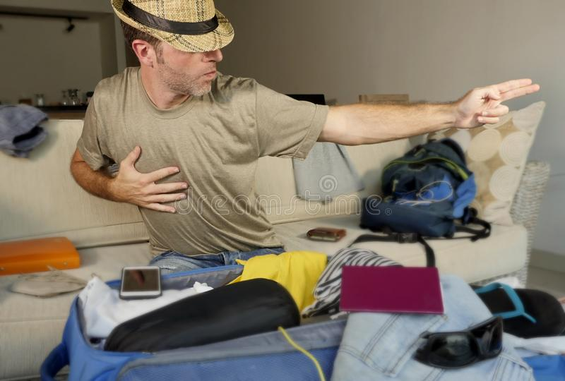 Young happy and excited man packing suitcase and backpack preparing for holidays travel using summer hat for imitating dancing pos. Ture of famous pop star stock image