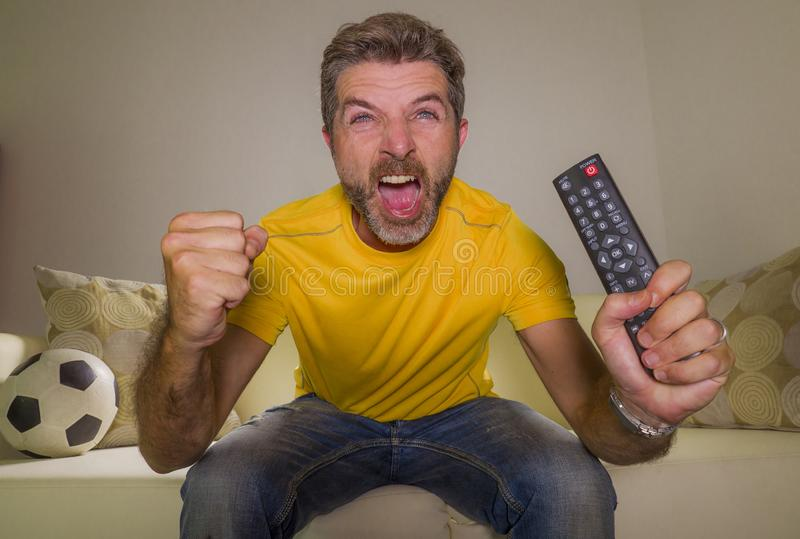 Young happy and excited man watching European football game on TV celebrating goal on couch screaming spastic gesturing crazy stock images