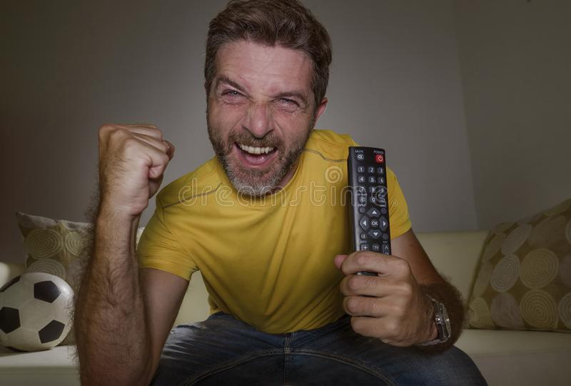 Young happy and excited man watching European football game on TV celebrating goal on couch screaming spastic gesturing crazy stock photos