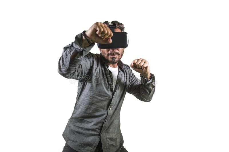 Young happy and excited man wearing virtual reality VR goggles headset experimenting 3d illusion playing fight or boxing video. Game enjoying punching isolated royalty free stock photo